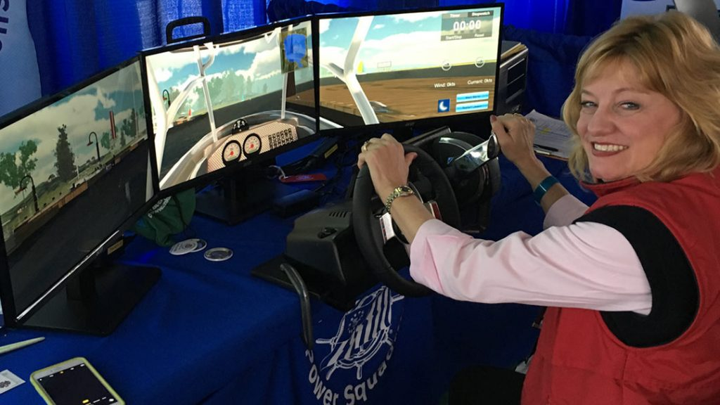 Boating Skills Virtual Trainer with student at the wheel in front of computer screens
